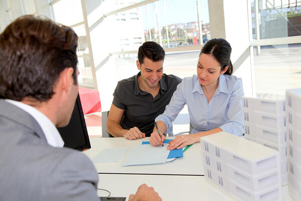 A man and a woman signing paperwork