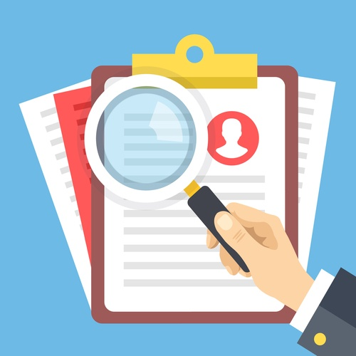 hand holding a magnifying glass looking at background check documents