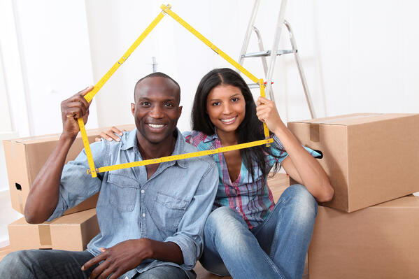A man and a woman are sitting in front of boxes and holding a house-shaped frame around them