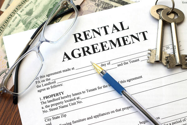 A rental agreement form with glasses, keys, a pen, and cash