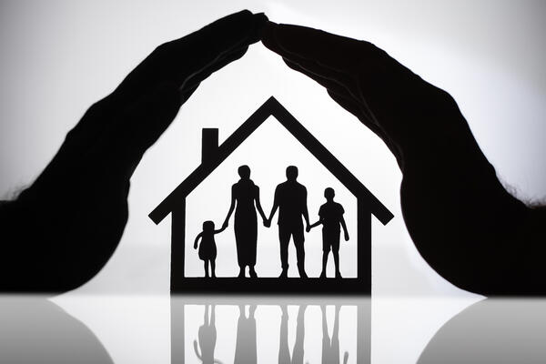 family with children silhouette inside black house outline