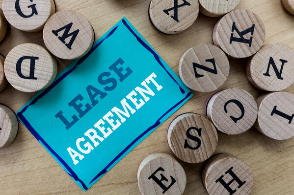 """A blue card with """"Lease Agreement"""" on it surrounded by round, wooden letter."""
