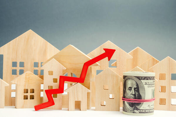 wooden houses with red arrow, one hundred dollar bill rolled up money