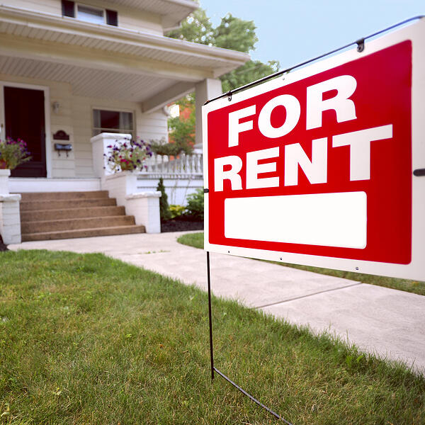 """A house with a """"for rent"""" sign in front"""
