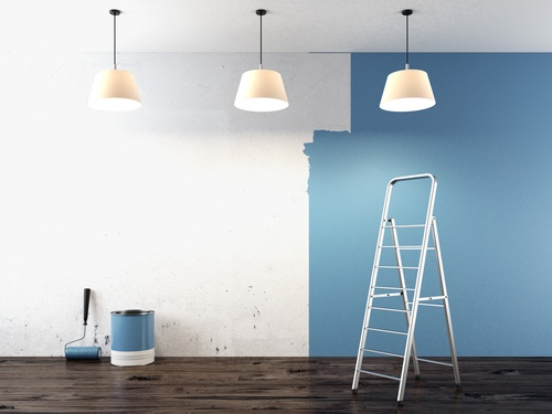 Room being painted blue with a ladder, paint bucket, and paint roller.