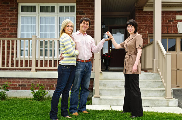 Woman handing keys to a couple standing in front of a house