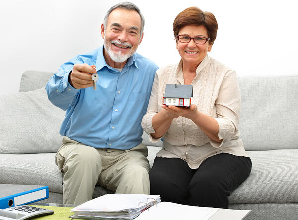 An older man and woman holding keys and a model house while sitting on a couch