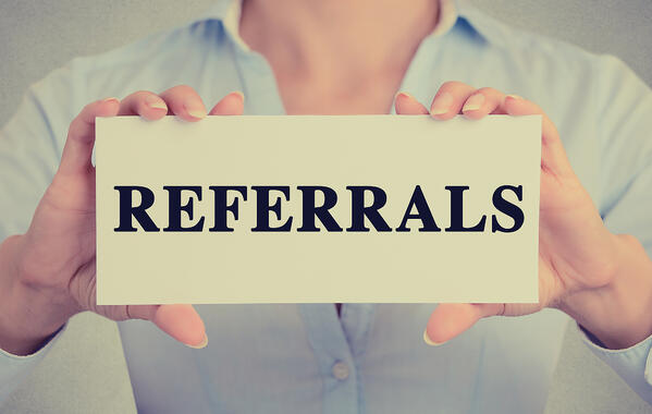 "Person holding paper with ""REFERRALS"" on it"