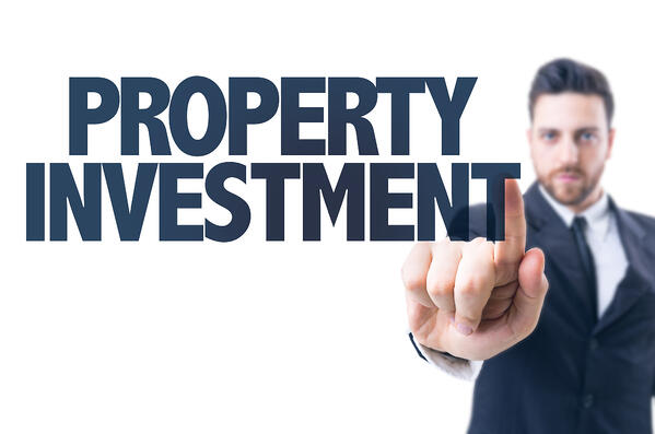 """A man is pointing to the words """"property investment"""""""