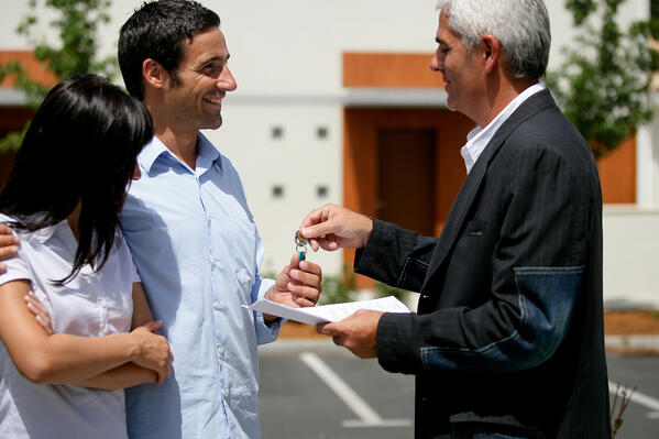 A man holding paperwork and keys is standing next to a man and a woman