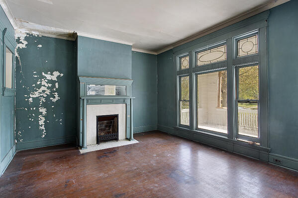 An empty room with a fireplace that has a damaged mantle, scuffed and dirty hardwood floors, and teal paint on the wall that has white showing through.