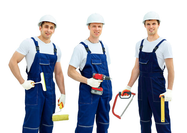 Three men in hardhats and overalls holding tools