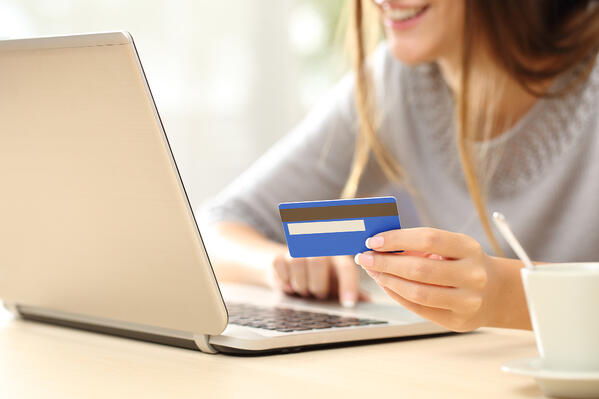 A woman holding a credit card making a payment on a laptop