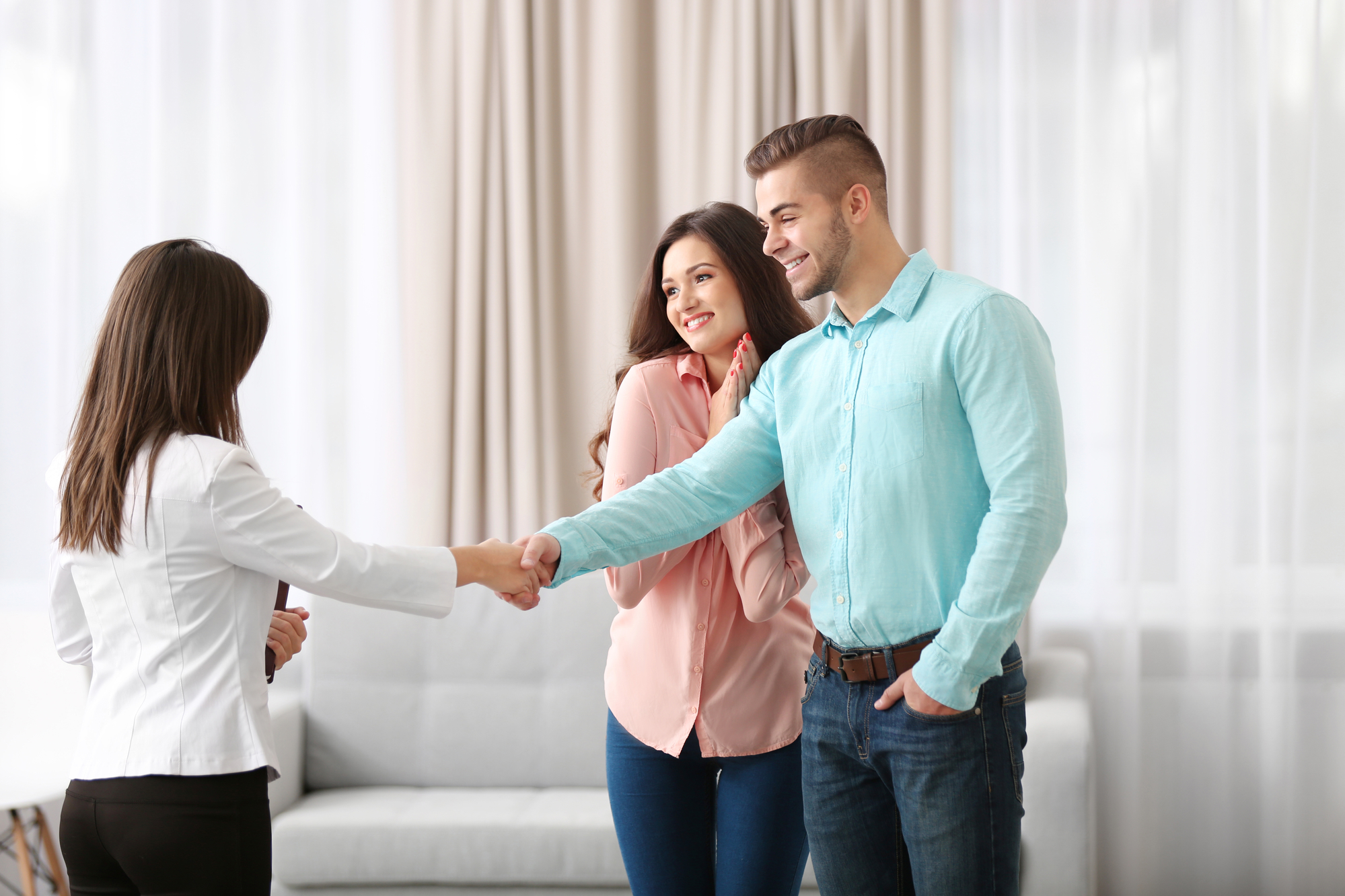 A man and a woman happily shake hands with another woman