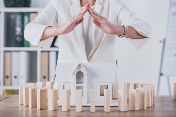 Partial view of risk manager covering house model surrounded with wooden blocks with hands