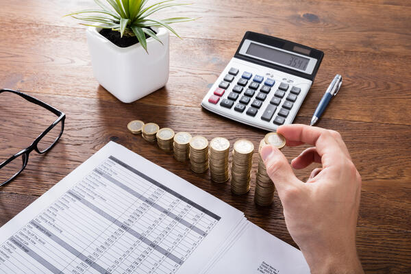 Person Stacking Coins On Desk