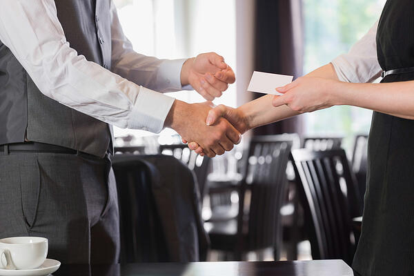 Business people shaking hands after meeting and changing cards in restaurant