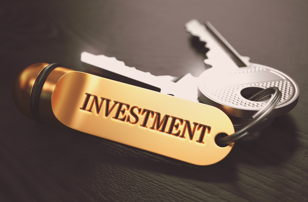 Keys with Word Investment on Golden Label over Black Wooden Background. Closeup View